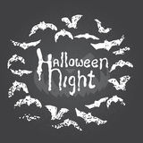 Hand drawn chalk lettering on chalkboard. Happy halloween postcard with round bat frame. Stock Photo