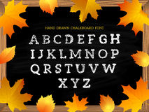 Hand drawn chalkboard font on autumn leaves background. Stock Photos