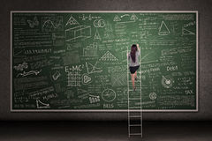 Hand drawn chalkboard with woman climb. Businesswoman is climbing a ladder looking at hand drawn chalkboard in a classroom Royalty Free Stock Photo