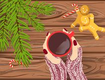 Hand drawn Christmas vector background, Hands in knitted gloves holding red cup of coffee on brown wooden table with chritmas tree. Branches, candy canes stock illustration