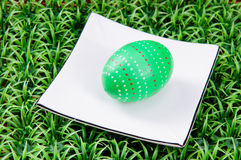 Hand-drawn Easter egg. Hand-drawn green Easter egg with plate on on artificial green grass Royalty Free Stock Image