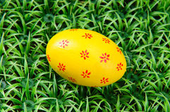 Hand-drawn Easter egg. Hand-drawn yellow Easter egg on on artificial green grass Stock Images