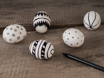 Hand drawn easter eggs with a pen on a wooden table Royalty Free Stock Images