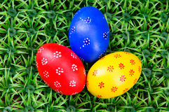 Hand-drawn Easter eggs. Three hand-drawn colorful Easter eggs on on artificial green grass Stock Images