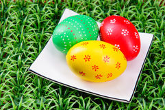 Hand-drawn Easter eggs. Three hand-drawn  Easter eggs with plate on on artificial green grass Stock Photo