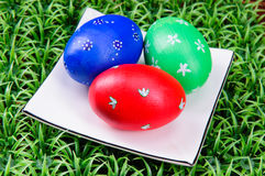 Hand-drawn Easter eggs. Three hand-drawn  Easter eggs with plate on on artificial green grass Royalty Free Stock Image