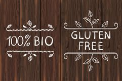 Hand drawn elements on brown wood. Gluten free and 100 percent BIO. VECTOR illustration. Hand drawn elements on brown wooden background. Gluten free and 100 Stock Photo