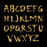 Hand drawn glitter golden alphabet in calligraphy brush Stock Photography