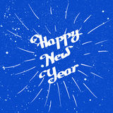 Hand-drawn Happy New Year with ink beam over blue Stock Image