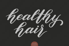 Hand drawn lettering - healthy hair. Elegant modern handwritten calligraphy. Vector Ink illustration. Typography poster Royalty Free Stock Photos