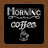 Hand drawn lettering `Morning coffee` with charcoal effect and view of a cup of coffee on black and brown wood background. Hand drawn lettering `Morning coffee Stock Photography