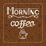 White Hand drawn lettering `Morning coffee` with charcoal effect and view of a cup of coffee on brown wood background. Hand drawn lettering `Morning coffee` Royalty Free Stock Images