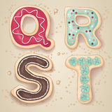 Hand drawn letters of the alphabet Q through T. In the shape of delicious and colorful cookies Stock Photos