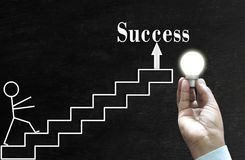 Hand drawn man climbing the steps to success. Shining bulb holding human hand and Hand drawn man climbing the steps to success Stock Photo