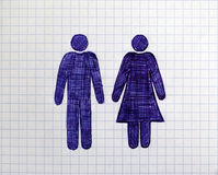 Hand drawn man and woman figures on the sheet of checkered paper Royalty Free Stock Image