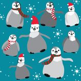 Penguins with christmas hats and scarfs with snowflakes seamless pattern. Vector illustration on blue background Stock Photos