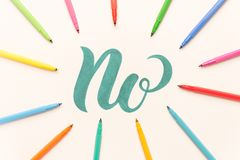 Hand drawn phrase NO isolated on white sheet. Green hand drawn phrase NO on white sheet between colorful markers. NO in frame of markers Royalty Free Stock Photo
