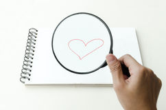 Hand-drawn red romantic heart. Drawn on a blank page in a sketch book and viewed through a magnifying glass held in the hand of a man, conceptual of love and Stock Images
