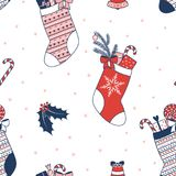 Seamless Christmas pattern. Hand drawn seamless vector pattern with Christmas stockings filled with presents, holly, bell, on a white background. Design concept Royalty Free Stock Photo