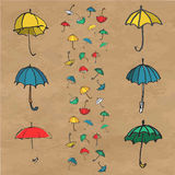 Hand drawn set of colorful umbrellas. Sketch illustration isolated on brown kraft paper background Stock Photography