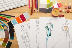 Hand drawn sketches for new fashion collection. New fashion collection background. Hand drawn sketches of clothes, color swatches and threads on wooden table Stock Images