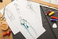 Hand drawn sketches for new fashion collection. New fashion collection background. Hand drawn sketches of clothes on white board, color swatches and threads, top Stock Image