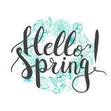 Hand drawn typography lettering phrase Hello Spring on the white background with blue blooming flowers wreath. Stock Image