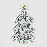 Hand drawn typography poster. Stylish typographic poster design with Christmas tree, inscription -We Wish You a Merry Christmas.. Retro colors. Inspirational Royalty Free Stock Images