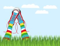 Hand drawn vector illustration his feet in sneakers and multicolored striped stockings sticking out of the grass Stock Images