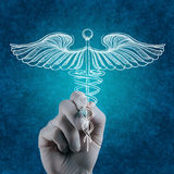 Hand draws Caduceus on white board. Doctor hand draws Caduceus on white board stock photo