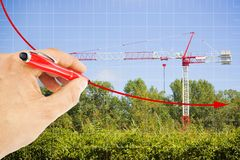 Hand draws a decreasing chart about building activity against a background with a tower crane in a construction site surrounded by. Nature - concept image vector illustration