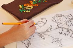 A hand draws a flower. With a pencil. Beautiful flowers needlework royalty free stock photography