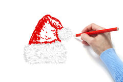 The hand draws a fur-cap. On a white sheet of a paper Royalty Free Stock Images