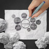 Hand draws gear business success chart concept on crumpled pape Stock Image