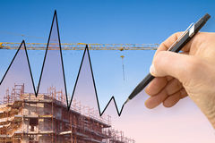 Hand draws a graph with a background of a construction site Stock Photo