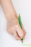 Hand draws by green crayon on sheet of paper Stock Photography