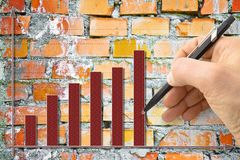 Hand draws a growing graph against a brick wall background - con. Cept image Stock Image