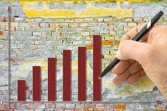 Hand draws a growing graph against a brick wall background - concept image royalty free stock image