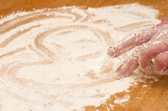 Hand draws heart on a flour Stock Photos