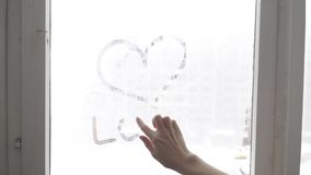 Hand draws love heart on cold fogged window background, closeup image. stock video footage