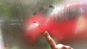Hand draws love heart shape on cold condensation window with water drops. Concept design for love or romantic stock footage