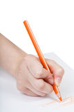 Hand draws by orange pencil on sheet of paper Stock Photo