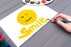 Hand draws smile on sheet Stock Images