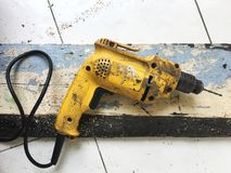 Hand drill machine. Yellow hand drill machine tool over grunge old weathered distressed wooden board workshop vintage bench on the floor stock photography