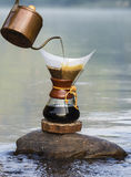 Hand drip coffee  on the rocks at the river Royalty Free Stock Images