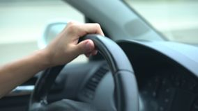 Hand of the driver on the car steering wheel while driving on the highway