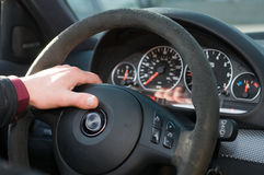 Hand of the driver on a steering wheel. Stock Photo