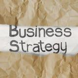 Hand drog ord för affärsstrategi på skrynkligt papper med revan Royaltyfri Fotografi