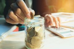 Hand drop the coin in jar with stack coins. Financial, accounting and saving concept. royalty free stock image