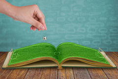 Hand drop football down to green grass Stock Photography